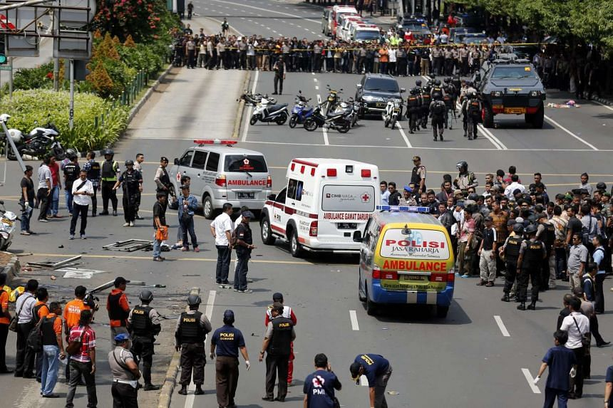 Indonesian police ambulances pass the crowds carrying victims to the hospital after the bomb blast in front of a shopping mall in Jakarta, Indonesia, Jan 14, 2016.