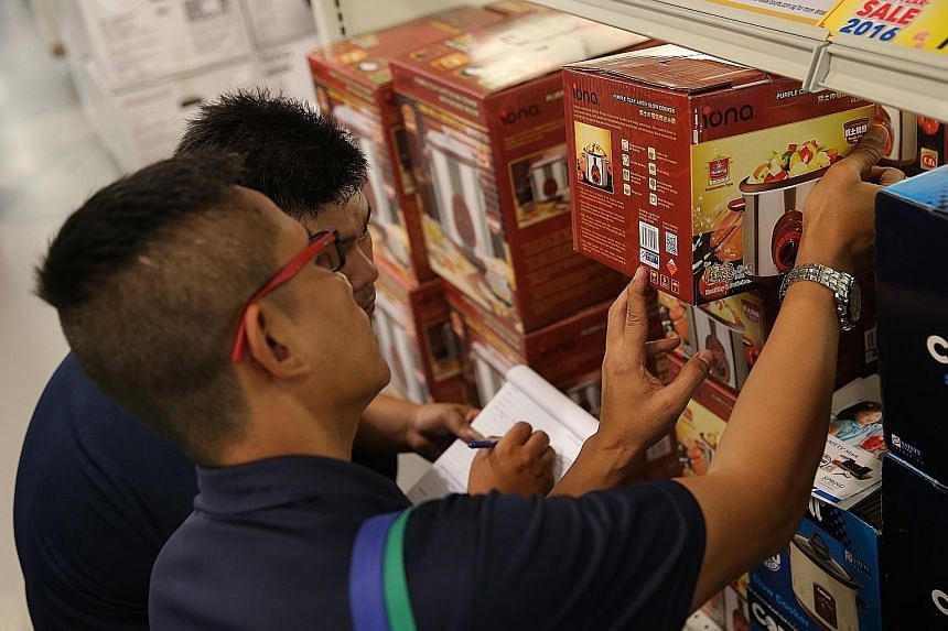 A sign (above) reminding consumers to look out for the accuracy label in measuring instruments used by retailers. Certis Cisco officers inspect safety marks on household appliances at the Courts Tampines Megastore (right).