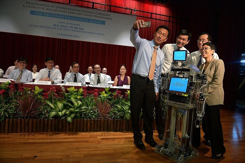 "Taking a wefie with ""Xuan"" the robot, a student project, yesterday were (from left) Mr Ong Ye Kung, Ngee Ann Polytechnic principal Clarence Ti, Energy Market Authority chief executive Ng Wai Choong and group director of WDA training partners group Go"