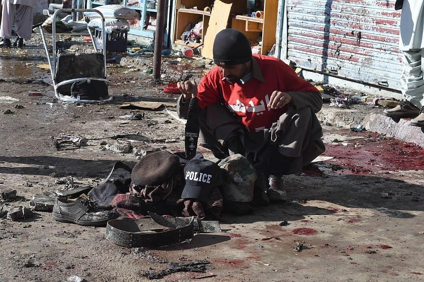 A volunteer collects the belongings of victims of the bomb blast. Policemen had gathered to accompany workers for a polio vaccination campaign in Quetta.