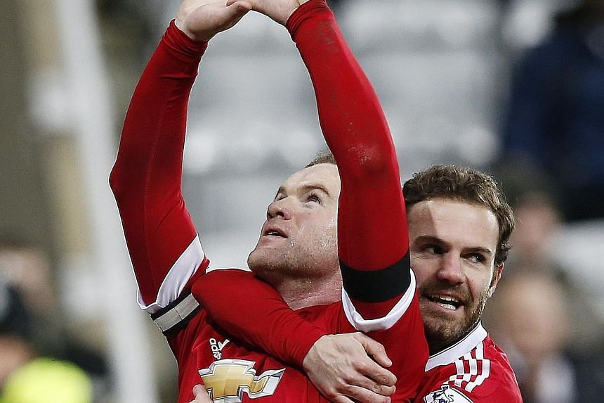 Wayne Rooney celebrating with Juan Mata after scoring the third goal for Manchester United against Newcastle.