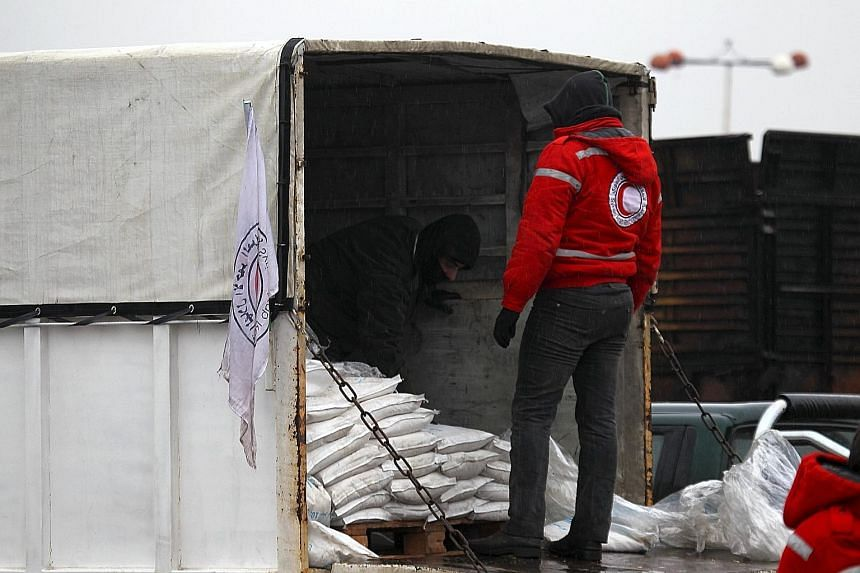 A rebel fighter inspecting aid supplies in Red Crescent vehicles on their way to Fouaa and Kfarya on Monday. Aid was also sent to Madaya, where people are reported to have died of starvation.