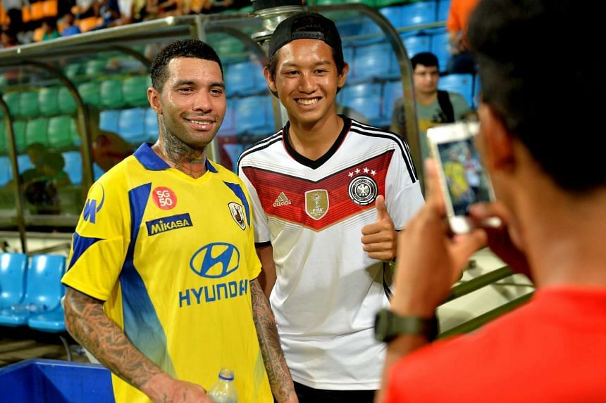 Jermaine Pennant (left) posing with one of his fans at a friendly match between Hougang United and Tampines Rovers at Jalan Besar Stadium on Jan 9, 2016.