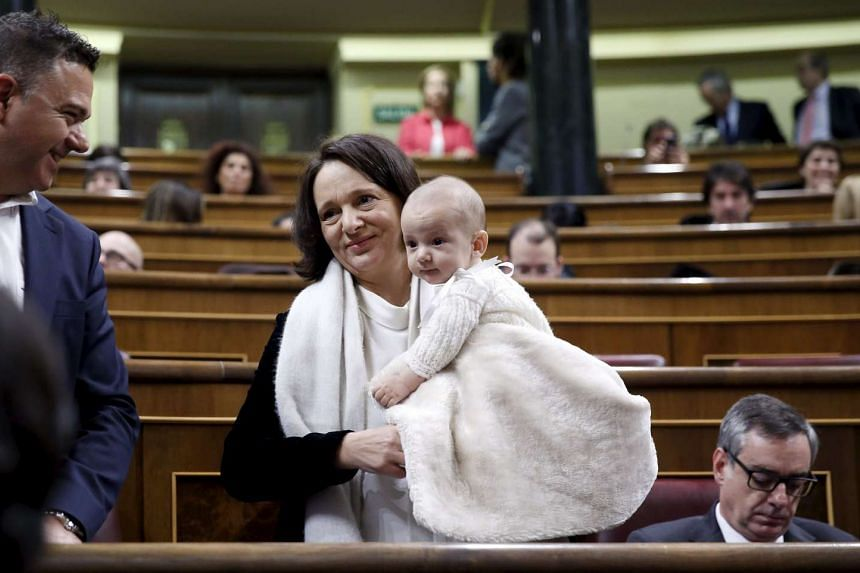 Podemos party deputy Carolina Bescansa holds up her son Diego as members of parliament take their seats on Wednesday.
