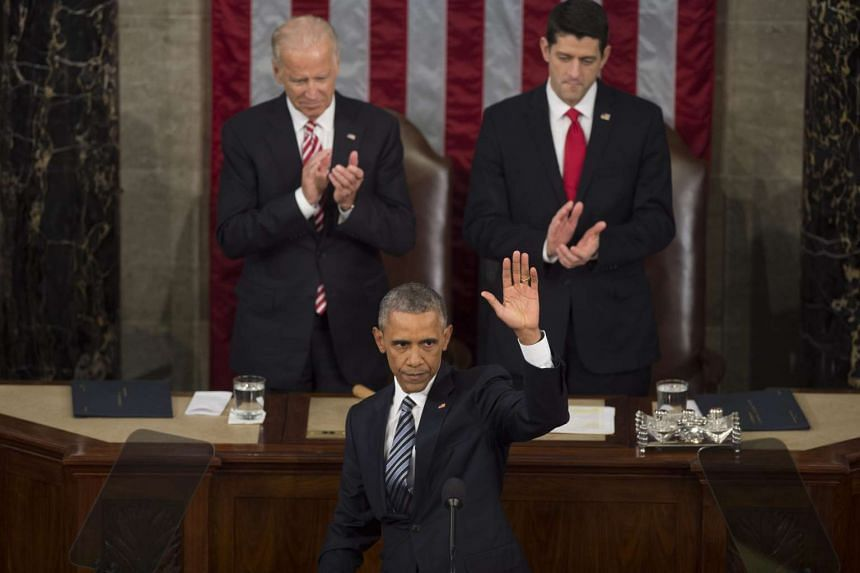 US President Barack Obama (centre) waves after delivering his final State of the Union address in the US Capitol, as US Vice President Joe Biden (left) and Speaker of the House Republican Paul Ryan (right) look on.