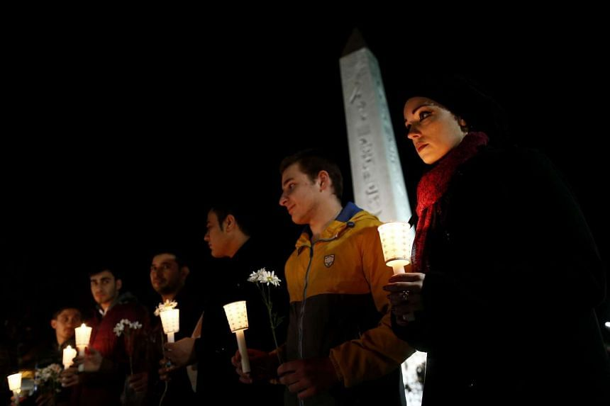 People hold candles and pray for victims who were killed in an explosion at the near by Sultanahmet in Istanbul on Wednesday.