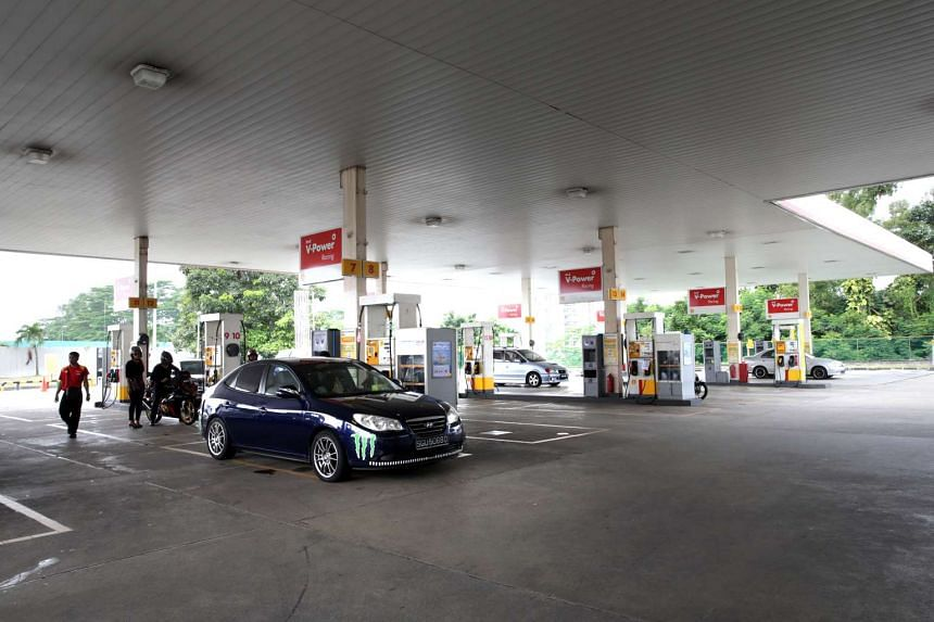 Cars topping up their fuel tanks at a Shell petrol station.