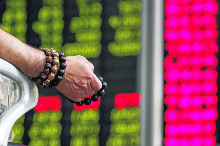 An investor holding onto prayer beads as he watches a board showing stock prices in Beijing.