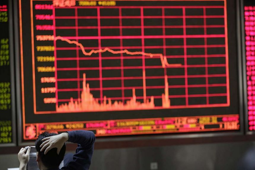 Investors looking at a screen showing stock movements at a brokerage house in Beijing on Jan 4.