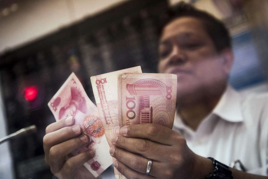 An employee at a currency exchange counting Chinese yuan banknotes in Hong Kong on Jan 12.