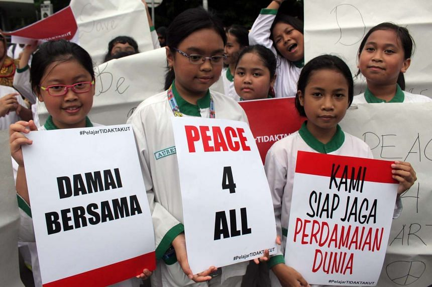 Indonesian students hold placards that say,  'Peace for all' and 'We are ready to protect world peace' during an anti-terrorist rally in Jakarta, Indonesia, on Jan 15, 2016.