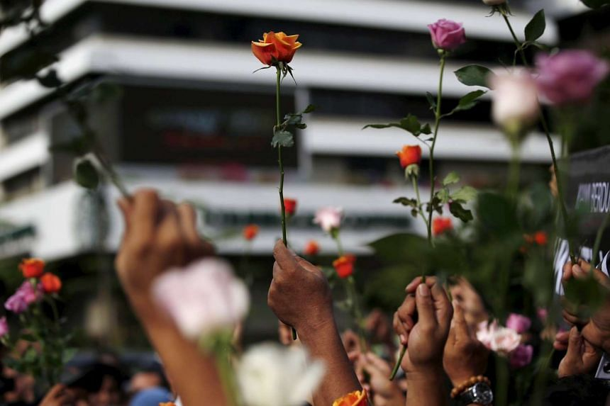 People hold flowers during a rally at the scene of Thursday's gun and bomb attack in central Jakarta, Indonesia on Jan 15, 2016.