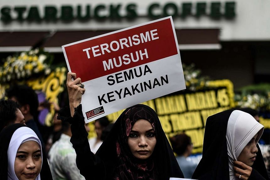 Women hold placards during a vigil outside the damaged Starbucks in Jakarta on Jan 15, 2016.