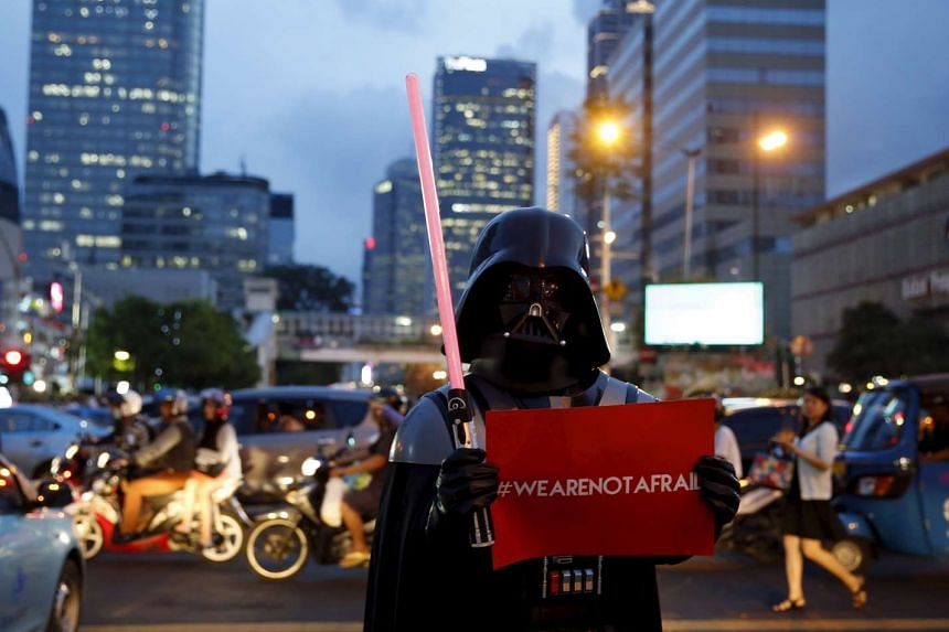 A man wearing Darth Vader costume holds a placard as he stands on the Thamrin street near the scene of Thursday's gun and bomb attack, in Jakarta, Indonesia, on Jan 15, 2016.