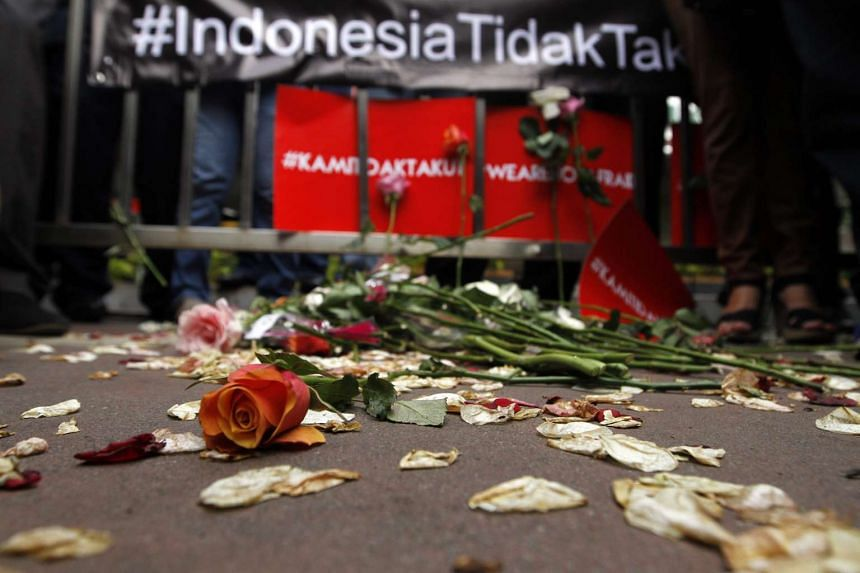 Flowers on the ground at the scene of a bombing attack that killed two civilians the day before, in Jakarta, Indonesia, on Jan 15, 2016.