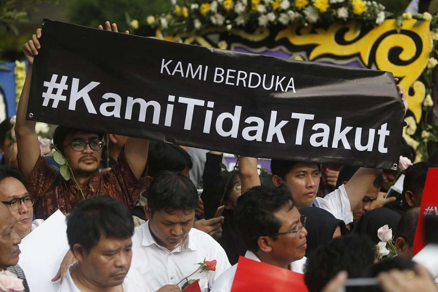 """Indonesian activists shout slogans and hold a banner reading """"We are not afraid"""" in front the site of a bombing in Jakarta."""