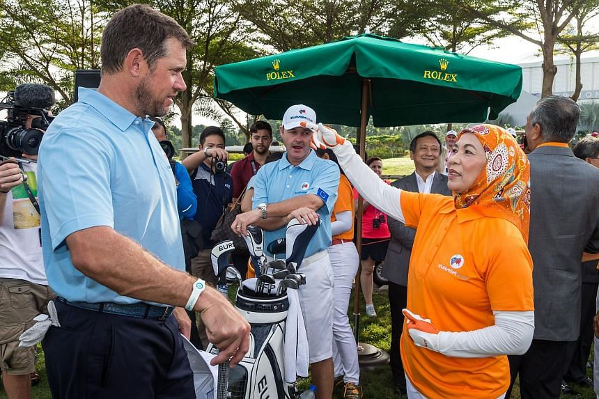 Lee Westwood (left) with Malaysia's Queen Haminah Hamidun during the final practice day of the EurAsia Cup golf tournament in Kuala Lumpur.
