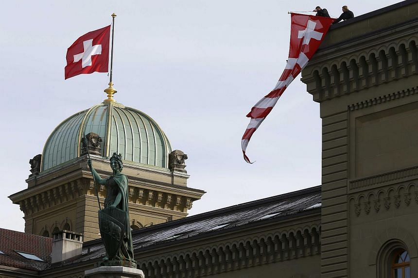 Workers hanging a Swiss flag on the parliament building in Bern on Nov 24, 2015.