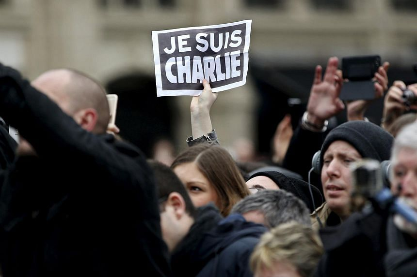 "A person holding a ""Je Suis Charlie"" sign at a ceremony on Jan 10 paying tribute to the victims of last year's shooting at the French satirical newspaper Charlie Hebdo."