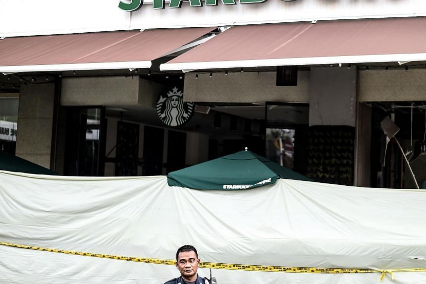 A security guard standing in front of the damaged Starbucks building in Jakarta on Jan 15.