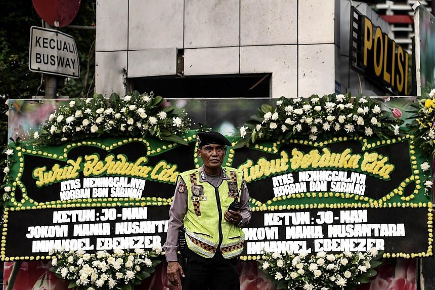 A traffic policeman standing in front of floral tributes set up at the blast site - a police outpost - in Jakarta on Jan 15.