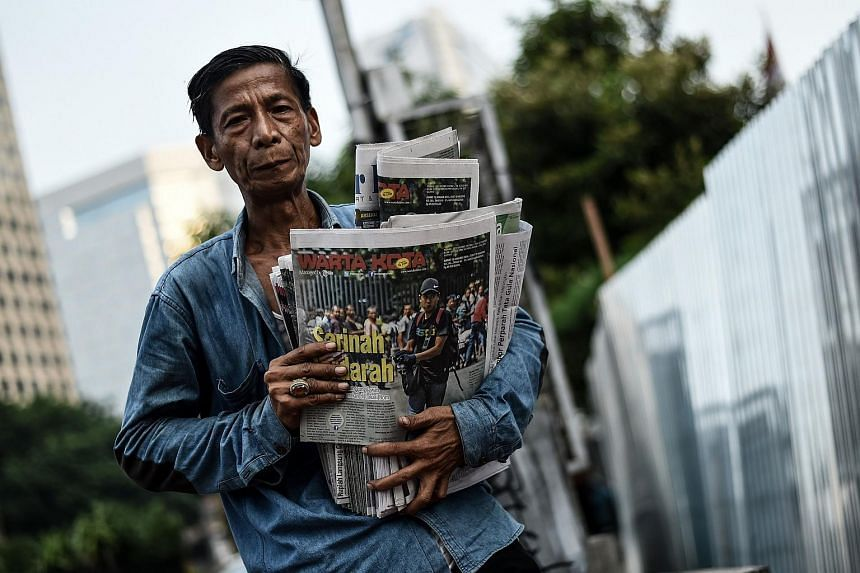 A man carrying newspapers bearing pictures of an alleged gunman in Jakarta on Jan 15.