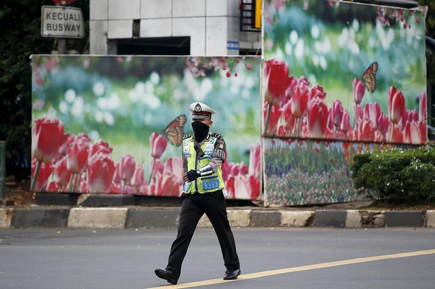 A police officer walking near a boarded up police box that was hit during yesterday's gun and bomb attack in Jakarta, on Jan 15.