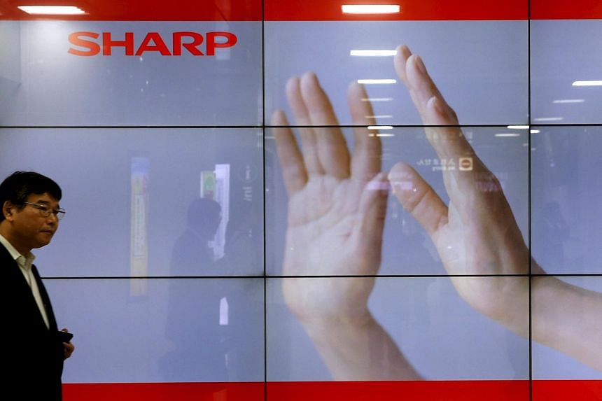 A man walking past a display showing a Sharp logo in Tokyo.