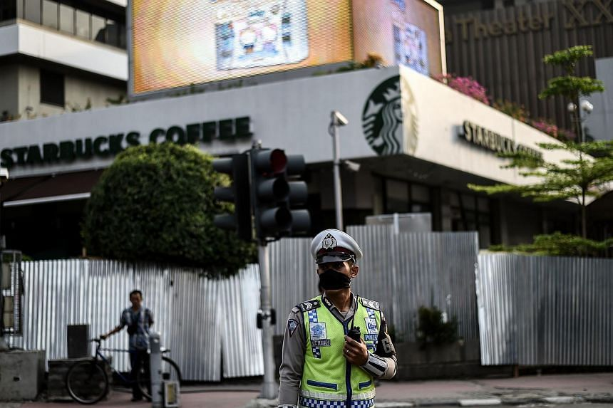 A policeman standing guard in front of the damaged Starbucks building in Jakarta on Jan 15.