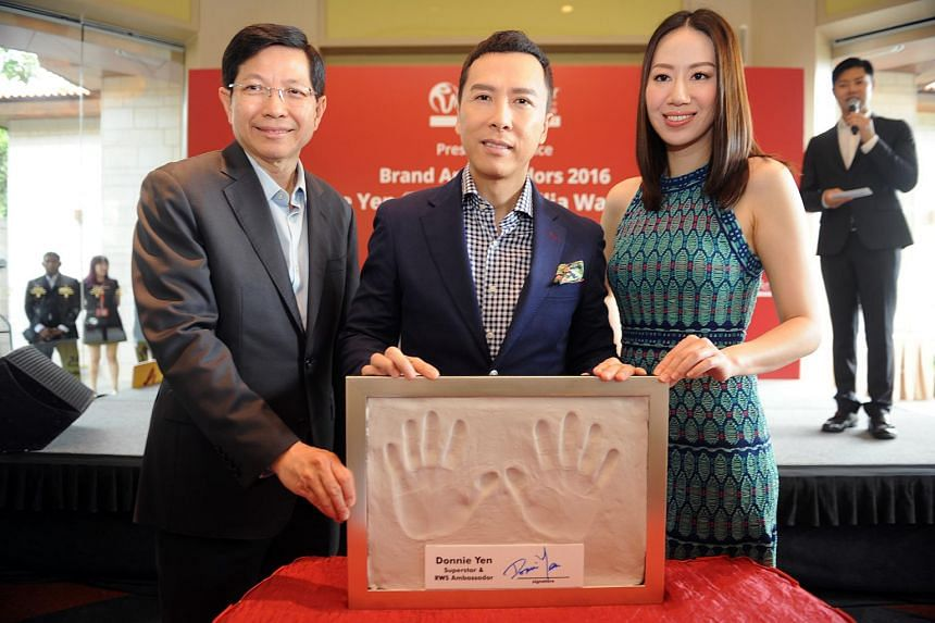 (From left) Chairman and CEO of Resorts World Sentosa Tan Hee Teck, and actor Donnie Yen and his wife Cecilia Wang holding up a mould with an imprint of Yen's hands.