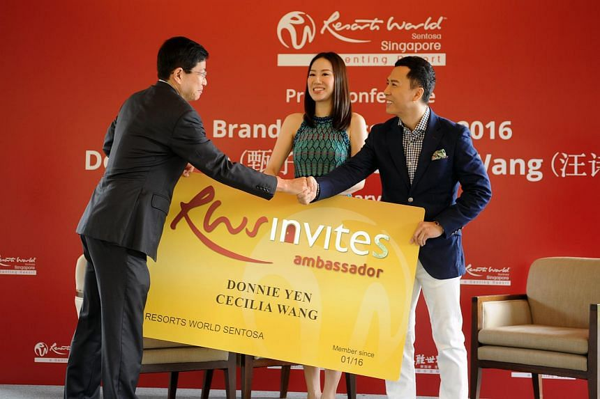 Chairman and CEO of Resort World Sentosa Tan Hee Teck (left) presenting the RWS invites to actor Donnie Yen (right) and his wife Cecilia Wang.