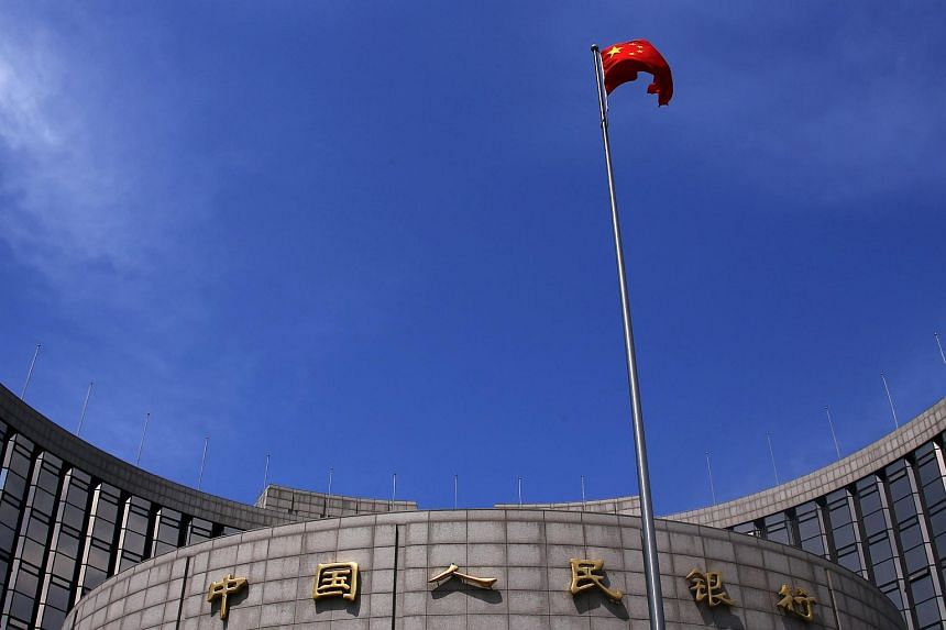 A Chinese national flag flutters in front of the headquarters of the People's Bank of China.