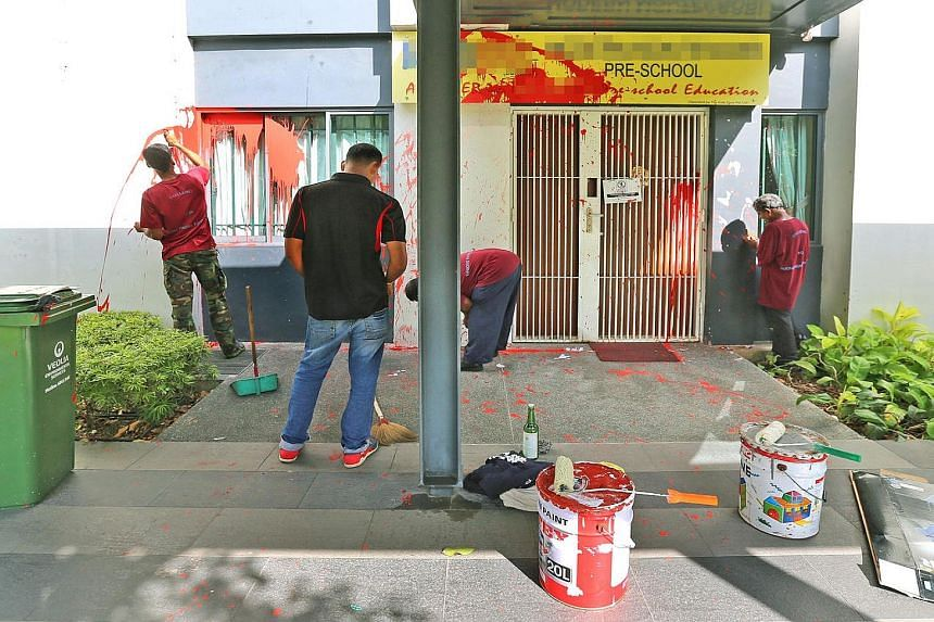 Workers attempting to scrub off the paint splashed at the Modern Montessori International at The Pinnacle@ Duxton yesterday. The incident has prompted unease among residents, one of whom said it was surprising that loan sharks would choose to target