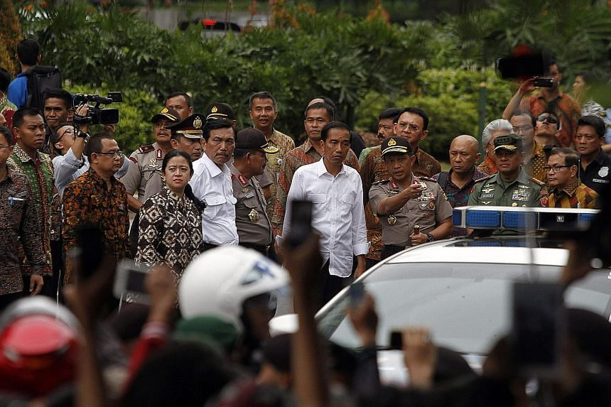 (Above) A police bomb squad member approaching the scene of an explosion following the terrorist attack in central Jakarta yesterday. (Right) Some of the weapons reportedly carried by the terrorists in the attack. Indonesian President Joko Widodo (ce
