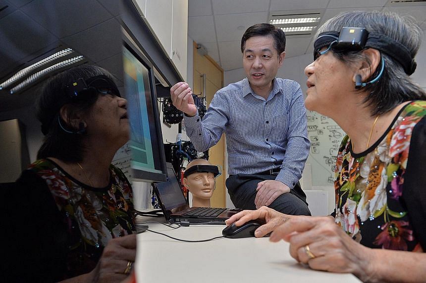 """(Above) Dr Joseph Simons is part of the team that created MoCHA, tablet games to detect dementia. (Right) Dr Guan (in blue) leads the team that developed a """"brain-computer interface"""" technology to train users' memory, concentration and other cognitiv"""