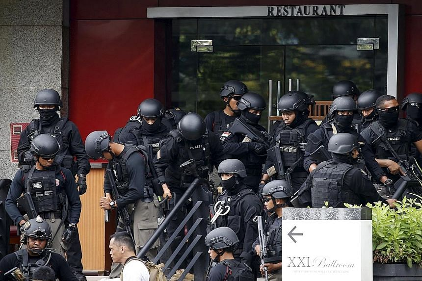 Indonesian police gathering outside a restaurant near the scene of the attack (above) and taking position (below) with their weapons as they pursued suspects outside a cafe yesterday. (Left) An injured foreigner lying on the ground outside the popula