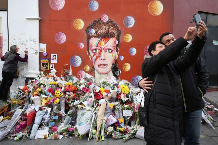 People take a selfie near floral tributes to David Bowie in London on Jan 13, 2016.
