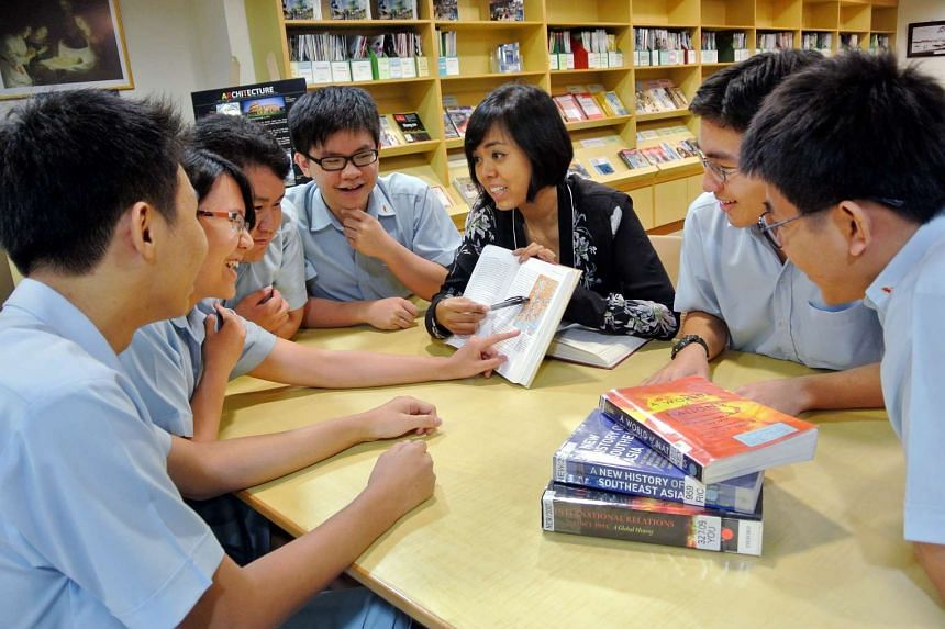 Catholic Junior College students in a discussion with their teacher Ms Nur Adhana Mohd Anwar.