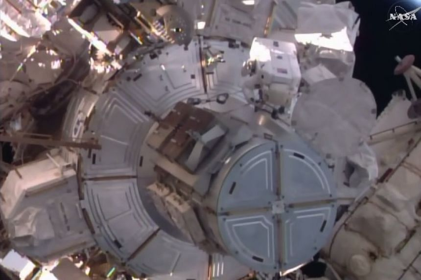 A screenshot of Tim Peake at work (top, right)  from Nasa TV.