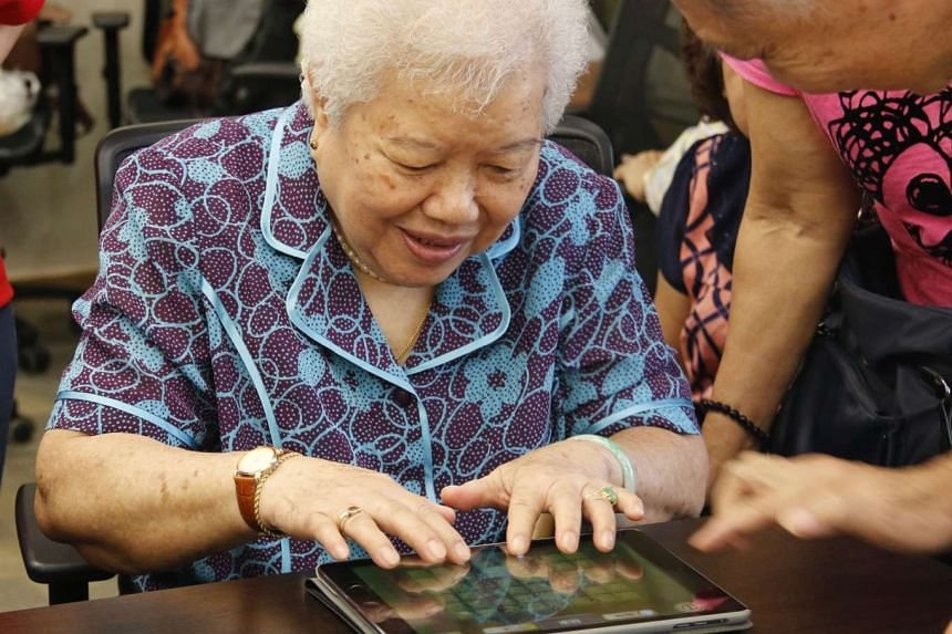 A woman plays a game developed by NTU's Research Centre of Excellence in Active Living for the Elderly (Lily) designed to detect movement problems - an example of technology that can give loved ones and healthcare professionals real-time information