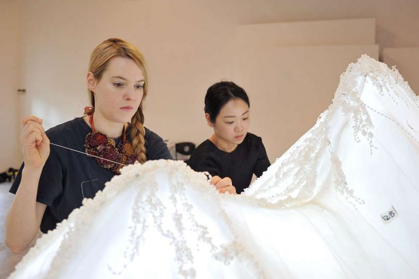 Sorcha O'Raghallaigh (left) and Sookoon Ang creating an installation in the shape of a mountain that is made from fabric.