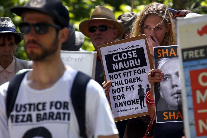 Protesters hold placards and listen to speakers during a rally in support of refugees in central Sydney, Australia.