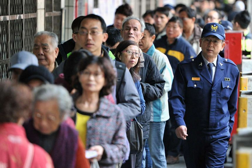 A police officer patrolling outside a polling station as residents line up to vote at the Xindian district in New Taipei City on Jan 16, 2016.