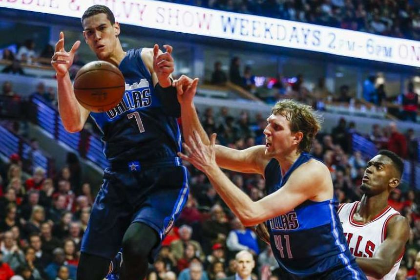 Dallas Mavericks forward Dwight Powell and Dirk Nowitzki reaching for a loose ball.