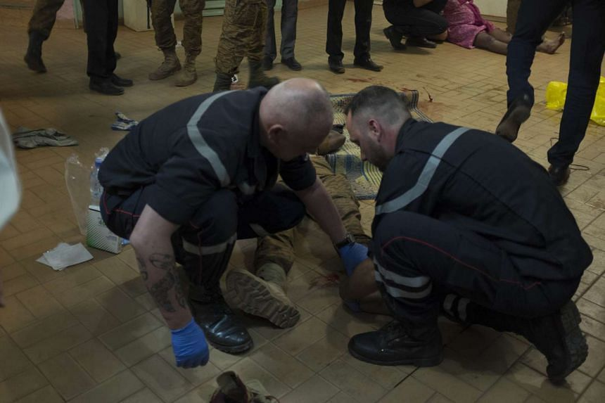 French gendarmes tend to wounded people in the surrounding of the hotel.