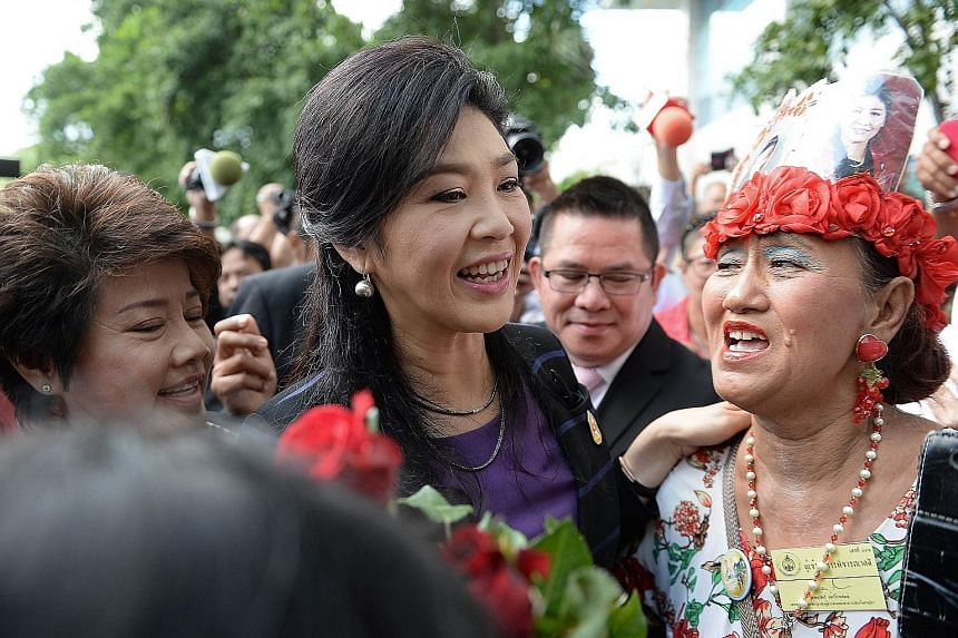 Ms Yingluck Shinawatra (left) being greeted by about 100 supporters outside the court yesterday.