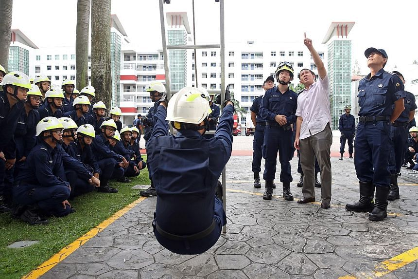 Mr Amrin observing a height rescue lesson for recruits (top) during a visit to the Civil Defence Academy yesterday morning. He then proceeded to prepare his speech at his office (above) before the swearing-in.