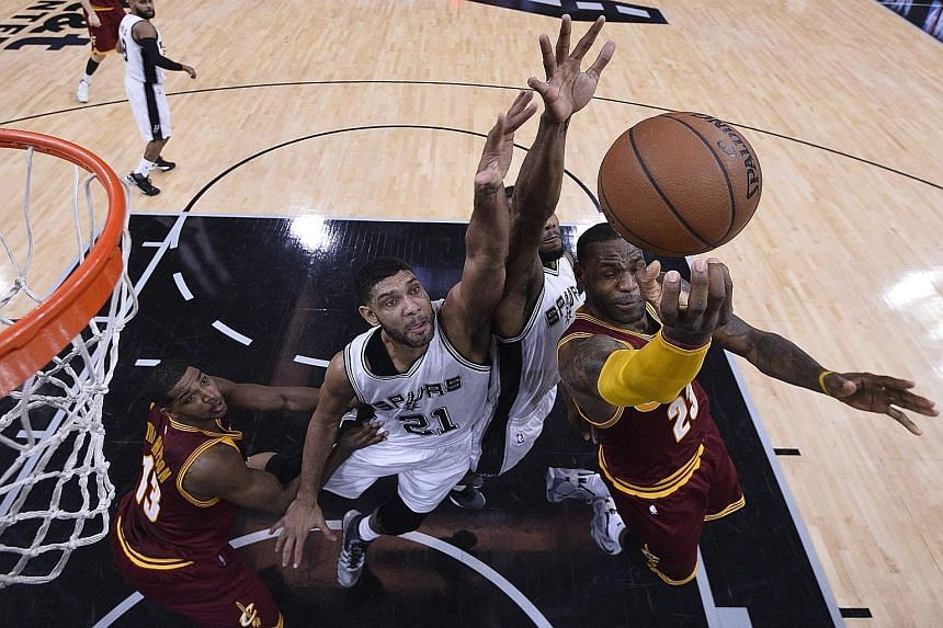 Cleveland's LeBron James (right) going up against San Antonio's Tim Duncan (centre) in the first half. The Spurs won the game 99-95.