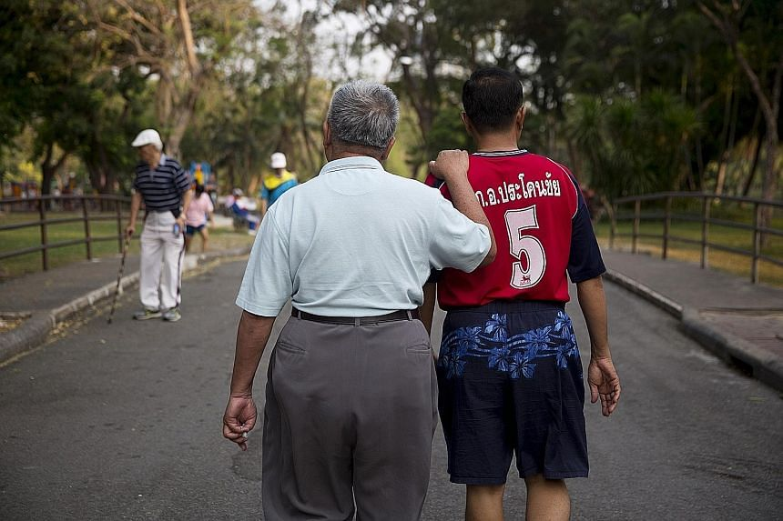 An elderly man holding another man's shoulder while walking through Lumpini Park in Bangkok. Households headed by the elderly are twice as likely to be poor as those headed by people in their 30s and 40s.