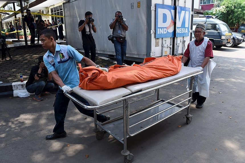Hospital workers wheeling away the body of a person who died in Thursday's attack, at Kramat Jati Police hospital in Jakarta yesterday. The blasts and ensuing shoot-out in downtown Jakarta left seven dead, of whom five were the attackers.